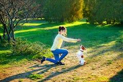 Giovane donna castana attraente che gioca con il suo cane in parco verde all'estate, concetto della gente di stile di vita Fotografia Stock