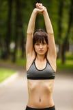 Giovane donna castana attraente che si scalda prima dell'allenamento di forma fisica Fotografia Stock
