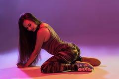 Giovane donna castana attraente nel ballo ballante del bottino dello studio su un fondo scuro immagini stock libere da diritti