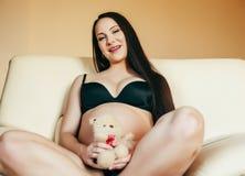 Giovane donna castana a casa in sedia incinta, la gente di stile di vita fotografia stock