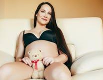Giovane donna castana a casa in sedia incinta, la gente di stile di vita immagine stock