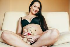 Giovane donna castana a casa in sedia incinta, la gente di stile di vita immagini stock libere da diritti