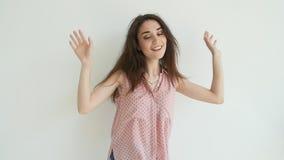 Giovane donna castana che balla sopra il fondo bianco video d archivio