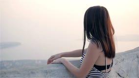 Giovane donna castana che cammina sul terrazzo e che gode del Mountain View archivi video