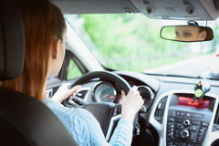 Giovane donna castana che conduce un'automobile Immagini Stock Libere da Diritti