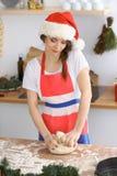 Giovane donna castana che cucina pizza o pasta fatta a mano mentre indossando il cappuccio di Santa Claus nella cucina Preparin d fotografia stock