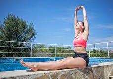 Giovane donna castana che fa esercizio di mattina vicino alla piscina o Immagine Stock Libera da Diritti