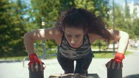 Giovane donna castana che fa i piegamenti sulle braccia dal banco al rallentatore di giorno soleggiato all'aperto - archivi video