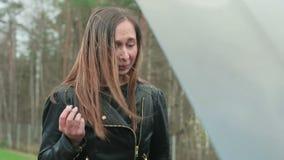 Giovane donna castana che grida e che fuma una sigaretta vicino al cappuccio di un'automobile rotta stock footage