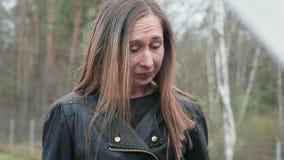 Giovane donna castana che grida e che fuma una sigaretta vicino al cappuccio di un'automobile rotta video d archivio