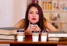 Giovane donna castana che indossa cima rosa che si siede dalla tazza della tenuta dello scrittorio che sembra stanca, tazze di ca Immagini Stock Libere da Diritti