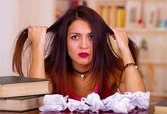 Giovane donna castana che indossa cima rosa che si siede dallo scrittorio con la pila di libri disposti su, tenendo capelli facen Fotografia Stock