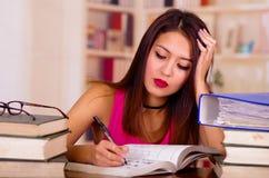 Giovane donna castana che indossa cima rosa che si siede dallo scrittorio con la pila di libri disposti su, testa di riposo sulla Fotografia Stock Libera da Diritti