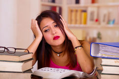 Giovane donna castana che indossa cima rosa che si siede dallo scrittorio con la pila di libri disposti su, testa di riposo sulla Fotografia Stock