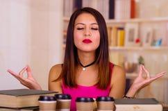 Giovane donna castana che indossa cima rosa che si siede dallo scrittorio con la pila di libri e di tazze di caffè disposti su, t Fotografia Stock Libera da Diritti