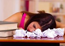 Giovane donna castana che indossa lo scrittorio chinato di menzogne della cima rosa con la pila di libri disposti su, carte sprec Fotografia Stock