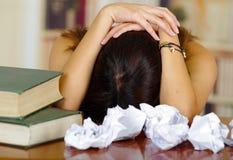 Giovane donna castana che indossa lo scrittorio chinato di menzogne della cima rosa con la pila di libri disposti su, carte sprec Fotografie Stock
