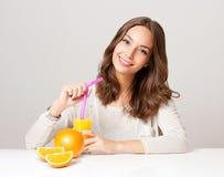 Giovane donna castana che mangia succo d'arancia fotografie stock libere da diritti