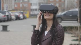 Giovane donna castana che ottiene esperienza di per mezzo della VR-cuffia avricolare o della cuffia avricolare di realtà virtuale video d archivio