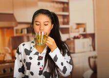 Giovane donna castana che posa nei pigiami e che affronta macchina fotografica mentre bevendo il tè di mattina felicemente Immagini Stock Libere da Diritti