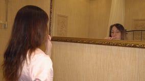 Giovane donna castana che pulisce i suoi denti davanti ad uno specchio archivi video