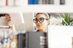 Giovane donna castana che sceglie libro in un deposito di libro Immagini Stock Libere da Diritti