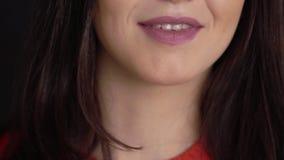 Giovane donna castana che sorride e che parla al fondo nero archivi video