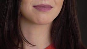 Giovane donna castana che sorride e che parla al fondo nero stock footage