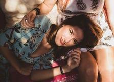 Giovane donna castana che sorride sulle gambe di un'altra donna fotografie stock