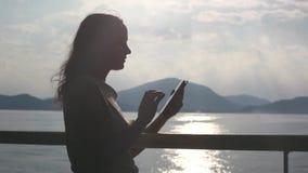 Giovane donna castana che sta sulla piattaforma della nave da crociera e che per mezzo del suo Smart Phone 1920x1080 archivi video
