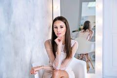 Giovane donna castana con capelli diritti e serici che si siedono davanti allo specchio Fotografia Stock