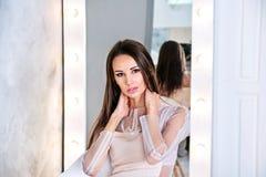 Giovane donna castana con capelli diritti e serici che si siedono davanti allo specchio sul fondo grigio con le mani sul collo Fotografia Stock