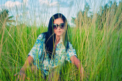 Giovane donna castana con gli occhiali da sole sul campo di erba verde Immagini Stock Libere da Diritti