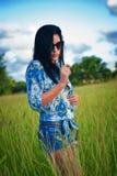 Giovane donna castana con gli occhiali da sole sul campo di erba verde Fotografia Stock Libera da Diritti