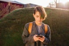 Giovane donna castana dai capelli corti attraente con il telefono in un parco immagine stock