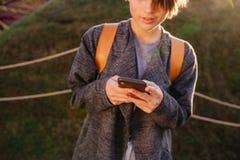 Giovane donna castana dai capelli corti attraente con il telefono in un parco fotografia stock libera da diritti