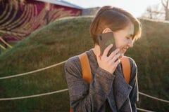 Giovane donna castana dai capelli corti attraente felice con il telefono in un parco immagini stock