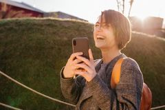 Giovane donna castana dai capelli corti attraente felice con il telefono in un parco fotografie stock