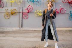 Giovane donna castana dai capelli corti attraente felice davanti alla parete della bicicletta fotografia stock libera da diritti