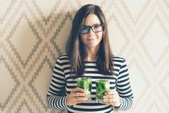 Giovane donna castana dei pantaloni a vita bassa in vetri con il frullato fotografie stock