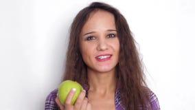 Giovane donna castana di sorrisi sani che mangia mela verde Movimento lento 3840x2160 video d archivio