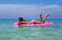 Giovane donna castana esile in occhiali da sole che nuota su un mattr dell'aria fotografie stock libere da diritti