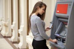 Giovane donna castana felice che ritira soldi dalla carta di credito a Immagini Stock Libere da Diritti