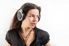 Giovane donna castana in grandi cuffie che ascolta la musica e divertiresi fotografia stock