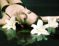 Giovane donna castana graziosa in acqua con il fiore del giglio, conce della stazione termale fotografia stock