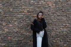 Giovane donna castana moderna alla moda in un cappotto lungo elegante nero in una maglietta alla moda nella posa bianca dei jeans immagine stock