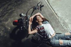Giovane donna castana sensuale che posa sul motociclo Immagine Stock