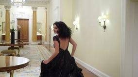 Giovane donna castana sexy in vestito uguagliante nero che corre nel palazzo o nell'hotel stock footage
