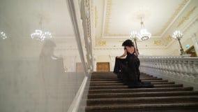 Giovane donna castana sexy in vestito uguagliante nero che va di sopra alla scala di pietra di marmo in palazzo o in hotel archivi video