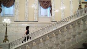 Giovane donna castana sexy in vestito uguagliante nero che va di sopra alla scala di pietra di marmo in palazzo o in hotel stock footage